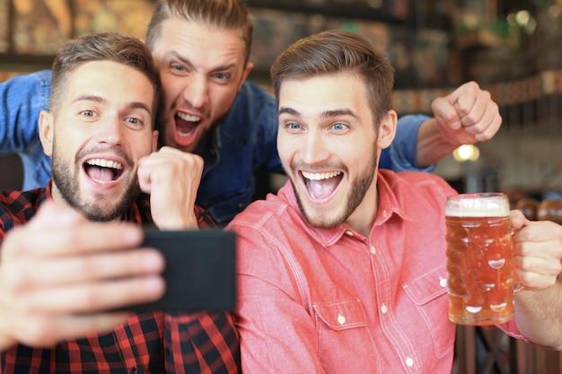 Diverse fußballfans, die fußball auf dem smartphone gucken und den sieg in der kneipe feiern.
