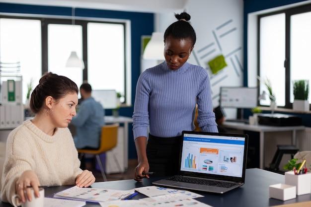 Diverse geschäftsfrauen, die über ein neues projekt für die unternehmensentwicklung diskutieren, schwarze frau, die aufgaben für einen neuen vertrag überprüft. multiethnische mitarbeiter versammelten sich im coworking space.