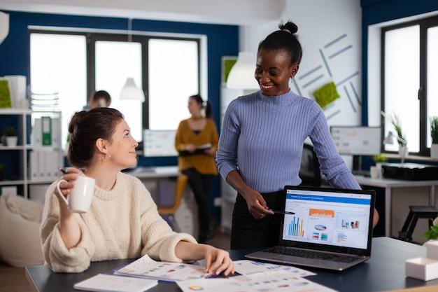 Diverse geschäftskollegen diskutieren über finanzstatistiken, lesen diagramme zu dokumenten des start-up-unternehmens