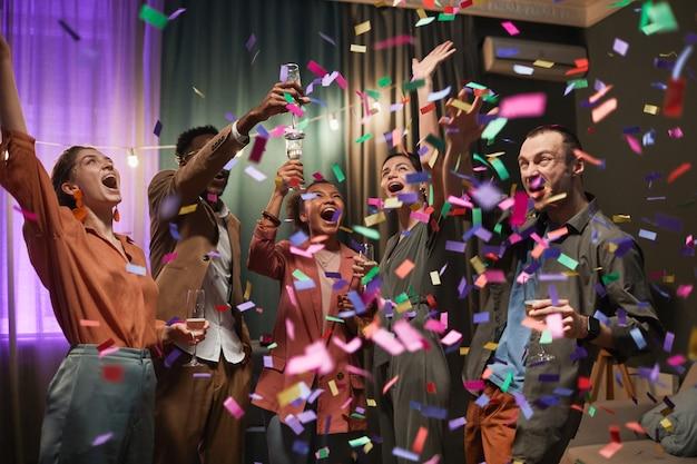 Diverse gruppe aufgeregter junger leute, die unter konfetti-dusche tanzen, während sie die party mit freunden drinnen genießen