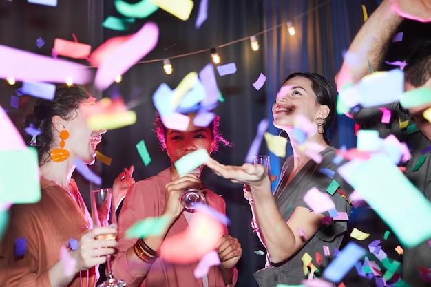 Diverse gruppe aufgeregter junger leute, die unter konfettidusche mit blitz tanzen