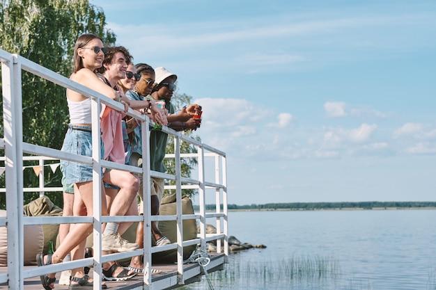 Diverse gruppe glücklicher freunde, die auf dem pier stehen und auf das wasser schauen