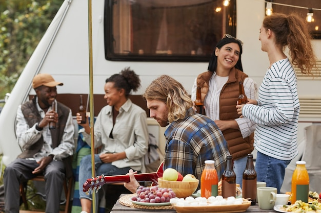 Diverse gruppe junger leute, die sich im herbst beim camping mit dem wohnwagen im freien entspannen