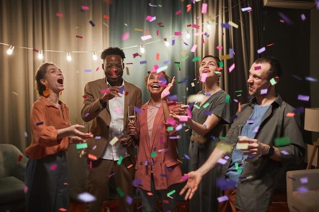 Diverse gruppe junger leute, die unter konfetti-dusche tanzen, während sie die party mit freunden drinnen genießen