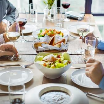 Diverse gruppe von erwachsenen essen, geselligkeit und diskutieren geschäfte
