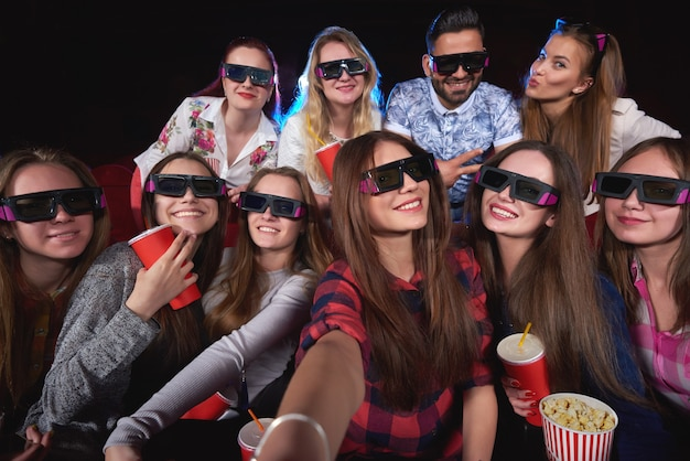 Diverse gruppe von freunden, die 3d-brillen tragen, die zusammen ein selfie machen, während im kino freundschaft freundschaft menschen zusammensein feier party wochenende treffen feiertage unterhaltsame einheit vielfalt.
