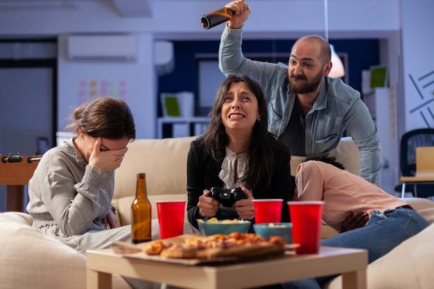 Diverse gruppe von freunden, die sich beim spielen von videospielen auf der tv-konsole verbinden und nach der arbeit mit dem joystick-controller verlieren. multiethnisches team genießt bürofeier mit snacks und getränken