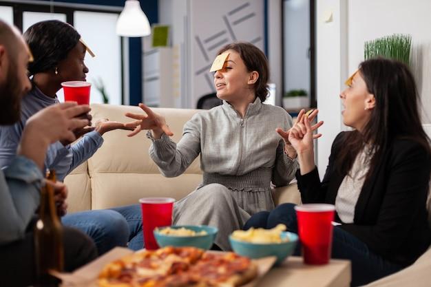 Diverse gruppe von freunden spielt nach der arbeit raten, wer spielt