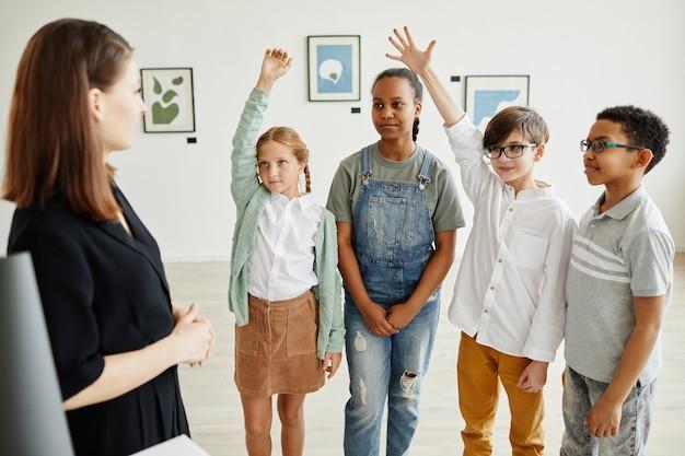Diverse gruppe von kindern, die hände heben, während sie der expertin in der galerie für moderne kunst zuhören