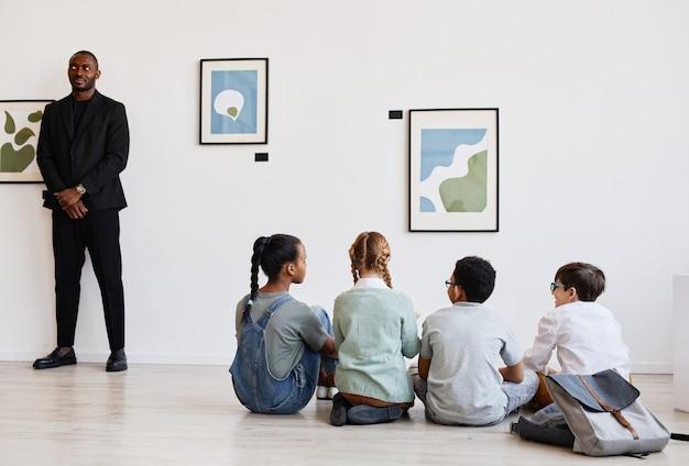 Diverse gruppe von kindern, die in der galerie für moderne kunst auf dem boden sitzen und gemälde diskutieren, raum kopieren
