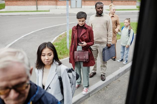 Diverse gruppe von menschen, die an der bushaltestelle mit sozialer distanzierung in der schlange stehen und in den bus einsteigen