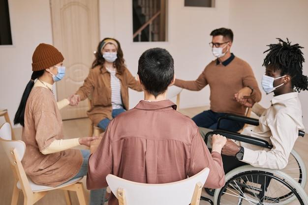 Diverse gruppe von menschen, die während der therapiesitzung händchen im unterstützungskreis halten und alle masken tragen