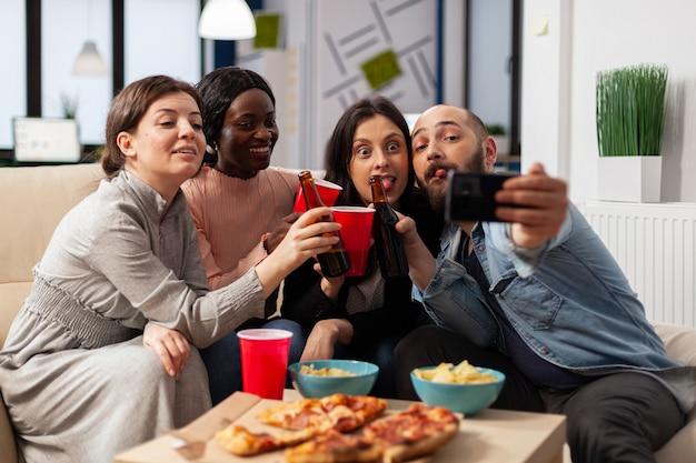 Diverse gruppe von mitarbeitern, die nach der arbeit auf einer büroparty ein selfie auf dem smartphone machen. fröhliche kollegen, die sich beim feiern mit pizzachips-flaschen und tassen bieralkohol amüsieren