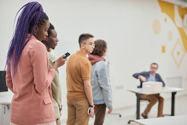 Diverse gruppe von studenten, die in der schlange stehen, um einen reifen college-professor in der schulaula zu konsultieren, platz zu kopieren