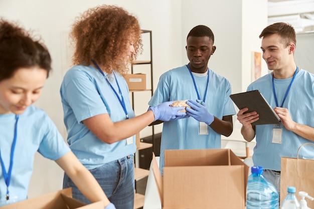 Diverse junge freiwillige in schutzhandschuhen beim sortieren der verpackung von lebensmitteln in kartons arbeiten
