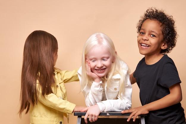 Diverse lächelnde positive kinder, die glücklich zusammen aufwerfen