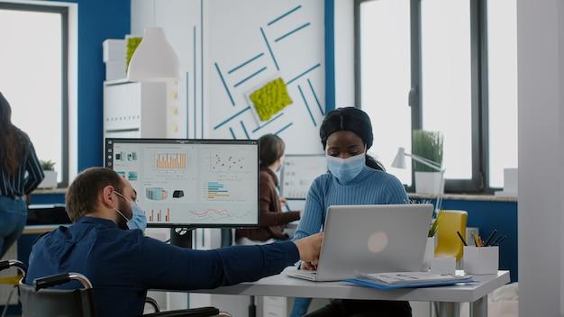 Diverse mitarbeiter mit schutzmasken, die während der pandemie an einem neuen normalen arbeitsplatz zusammenarbeiten, ungültiger manager mit behinderungen, der auf den laptop zeigt, der die unternehmensstrategie der frau erklärt