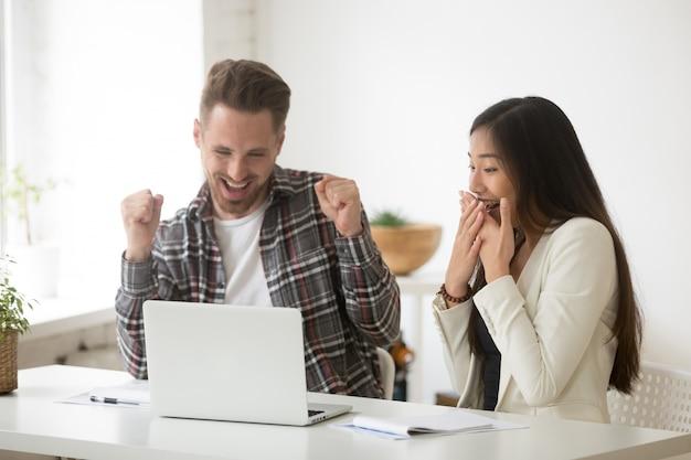 Diverse staunende kollegen, die von online-gewinn oder ergebniserreichung begeistert sind