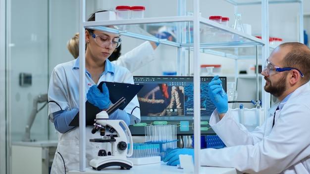 Diverses team von biochemie-wissenschaftlern, die medikamente gegen neue viren entwickeln, arzt, der proben überprüft, während krankenschwester notizen in der zwischenablage in einem modern ausgestatteten labor macht. multiethnische wissenschaftler arbeiten