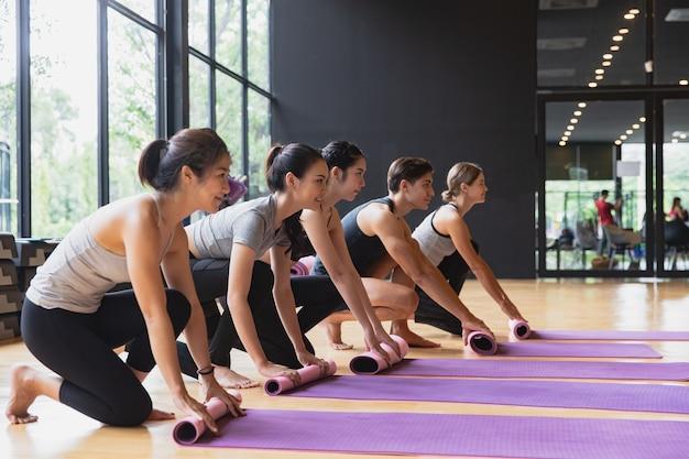 Diversity-gruppe von freundübungen yoga und training für meditation zusammen. sport-, fitness-, meditations- und entspannungskonzept