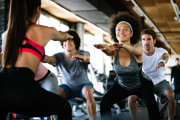 Diversity-gruppe von menschen, die in einem fitnessstudio trainieren. trainer und sportlich fitte personen, die in einem fitnesskurs trainieren
