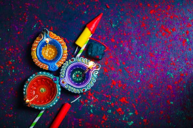 Diwali diya mit feuerwerkskörpern über rangoli