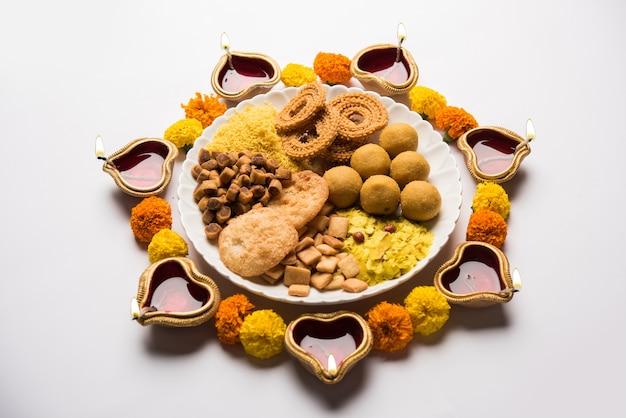 Diwali rangoli oder design aus indischen snacks oder süß und diya oder lampe und blumen
