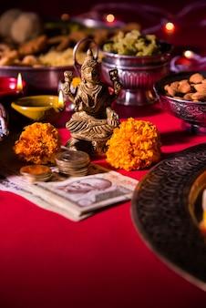 Diwali und zubereitung für laxmi oder lakshmi pooja mit elementen wie diya, geldscheinen, süßigkeiten, blumen, snacks, haldi und kumkum