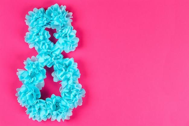Diy acht machte pappe verzierte künstliche blume, die blauen seidenpapierserviette-rosahintergrund gemacht wurde.
