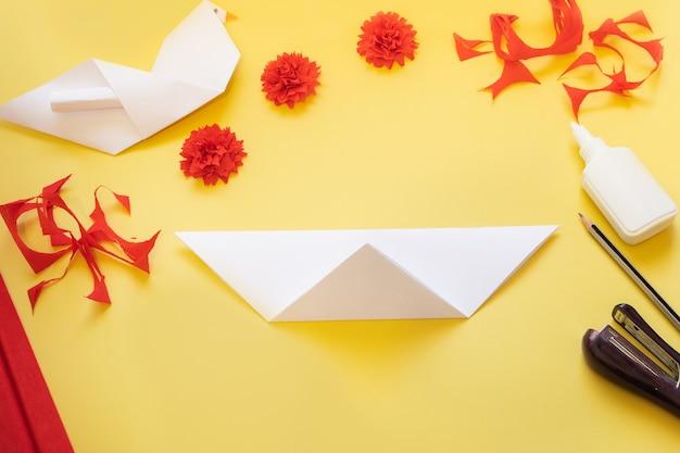 Diy anleitung. wie man eine karte mit nelkenblumen und origami-taube zu hause macht.