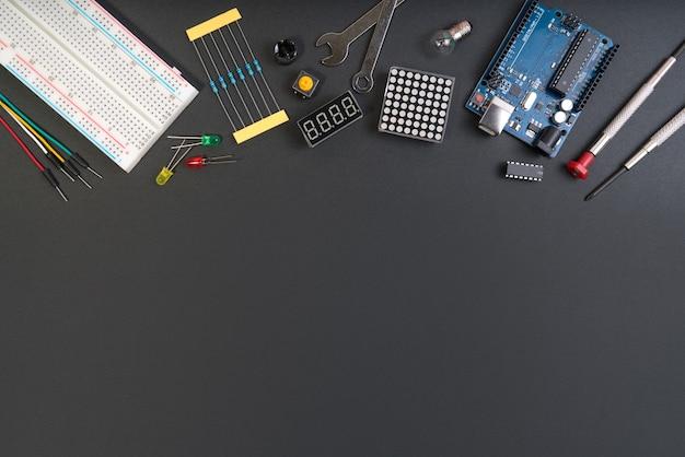 Diy elektronische hersteller bearbeitet komponenten auf schwarzem hintergrund.