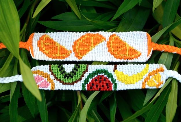 Diy freundschaftsbänder mit fruchtmustern auf grünen blättern