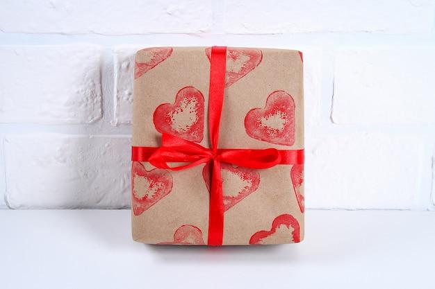 Diy. geschenkverpackung zum valentinstag. kraftpapiergeschenk und kartoffelstempel in form eines herzens