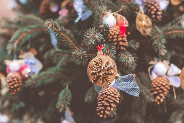 Diy handgemachte dekoration aus nudeln und tannenzapfen auf einem weihnachtsbaum