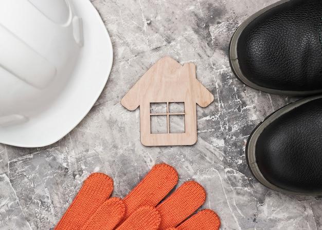 Diy heimwerkzeug. bau sparende ausrüstung und hausfigur auf grauem betonhintergrund. flache zusammensetzung. draufsicht