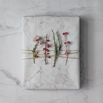 Diy hipster geschenk in marmor strukturiertes papier mit winterlaub eingewickelt. flach liegen.
