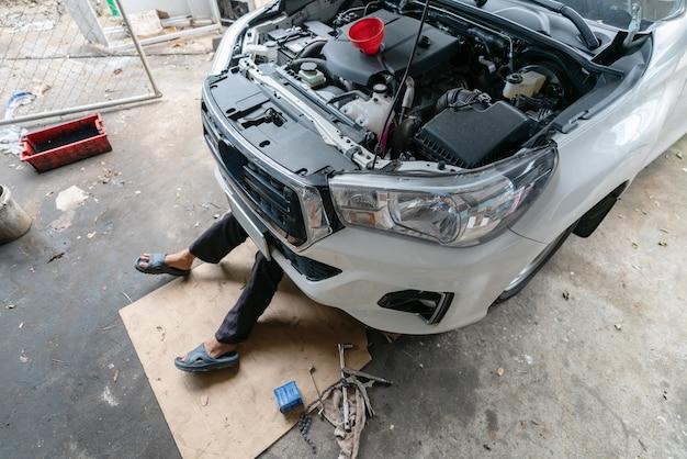 Diy-mechaniker, der zu hause unter garage des autos liegt und arbeitet