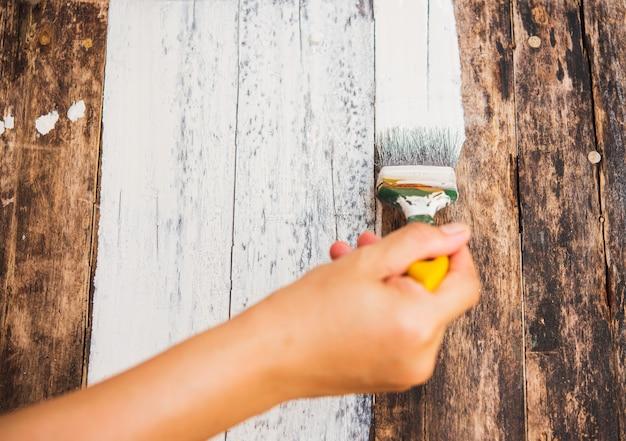Diy nahaufnahme frau hand mit pinsel dekorieren oder altes holz malen