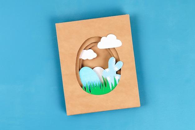 Diy osterkarten aus papier. volumengrußkarten mit einem häschen, ei auf blauem hintergrund. 3d.
