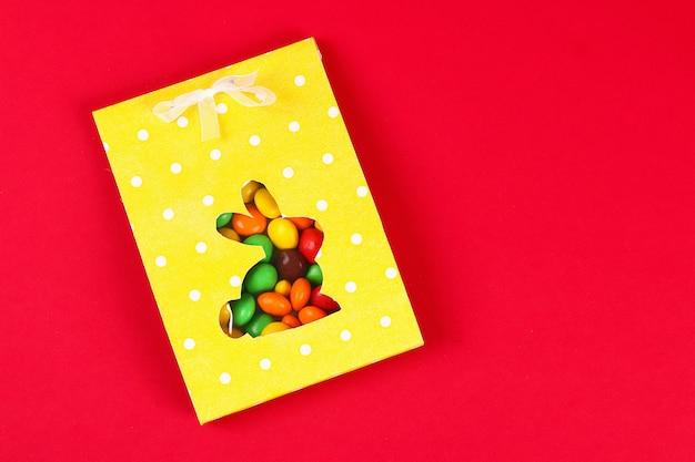 Diy ostern, der paketbonbons in einer tasche mit einem herausgeschnittenen häschenschattenbild auf einem roten hintergrund einwickelt.