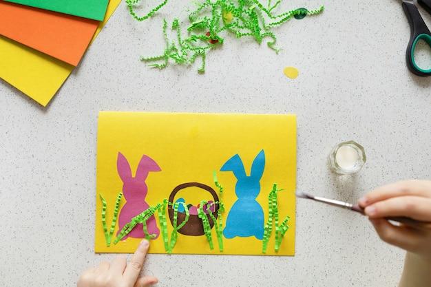 Diy postkarte schritt für schritt. karte glückliches ostern mit kinderhänden. bastelkonzept für kinder. schritt 8. kleben sie das gras von den zerknitterten papierstreifen auf den karton.