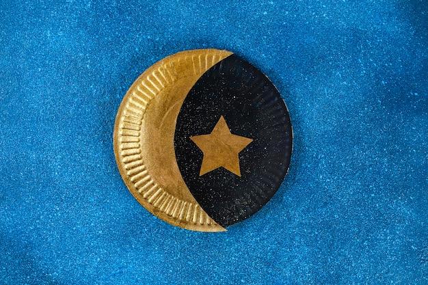 Diy ramadan kareem sichelförmiger mond mit einem stern von einem wegwerfpappteller und von einer goldfarbe.