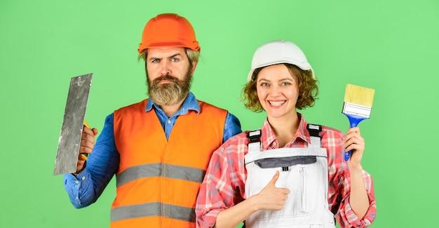 Diy-reparatur. bauarbeiter. renovierung des hauses. fröhliches paar, das haus renoviert. frauenbauer-schutzhelm. mann ingenieur oder architekt. innenrenovierung. familiennest. wände streichen. farbe wählen.