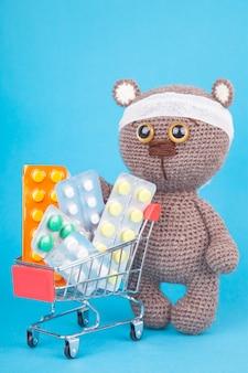 Diy spielzeug. gestrickter braunbär. einkauf für medikamente, gesundheitskosten und konzept der verschreibungspflichtigen medikamente mit einem einkaufswagen, der mit pillen gefüllt wird