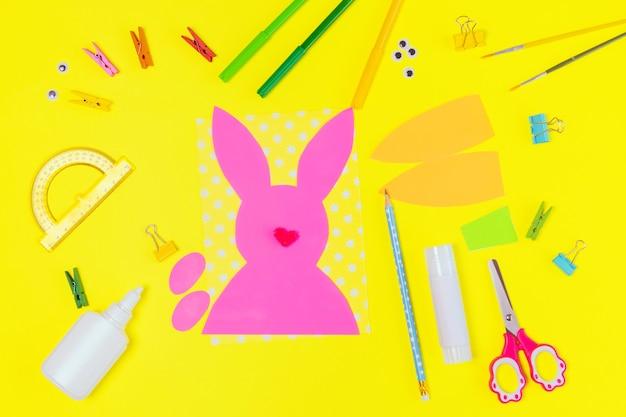 Diy und kinder kreativität. schritt für schritt anleitung: erstellen sie eine osterkarte mit hase und karotte. handgemachtes osterhandwerk für kinder. draufsicht schritt 1