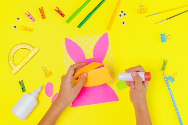 Diy und kinder kreativität. schritt für schritt anleitung: erstellen sie eine osterkarte mit hase und karotte. handgemachtes osterhandwerk für kinder. draufsicht schritt 2