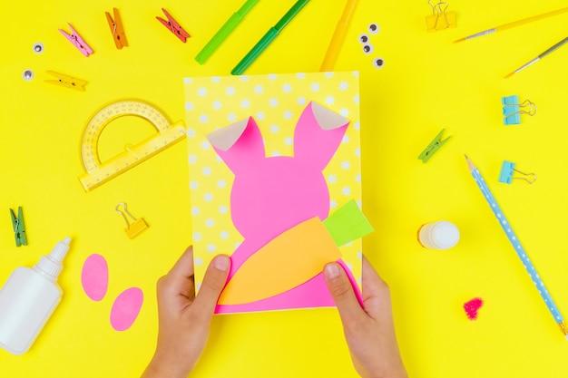 Diy und kinder kreativität. schritt für schritt anleitung: erstellen sie eine osterkarte mit hase und karotte. handgemachtes osterhandwerk für kinder. draufsicht schritt 3