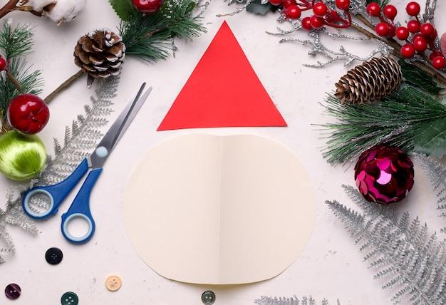 Diy weihnachtskarte schritt für schritt. aus farbigem papier und baumwolle falten sie das blatt in zwei hälften und schneiden sie den kreis auf den boden. aus einem anderen blatt papier ein dreieck.
