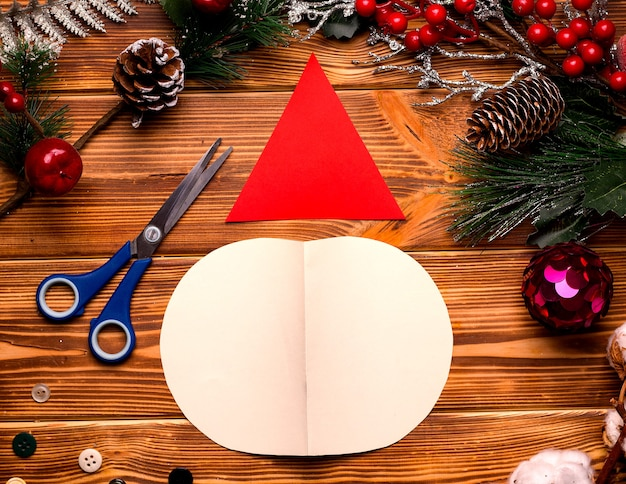 Diy weihnachtskarte schritt für schritt. aus farbigem papier und watte auf einem holztisch. schritt eins