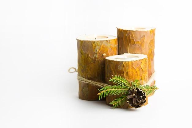 Diy weihnachtskerzenhalter aus kiefernstämmen, kerzen, bastelseil, tannenzweigen und zapfen. fertiges produkt, kerzen einsetzen und anzünden. dekoration des neuen jahres. schritt-für-schritt-anleitung flach legen, schritt 5.
